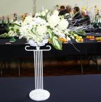 In a white cont. fresh arrang. placed on a tall stand  for buffet table